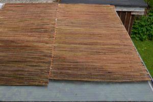 Blick von oben auf eine überdachte Pergola: Die Weidenmatten sind einfach aufgelegt und sorgen für Schatten unter dem Dach aus Stegplatten, die die Hitze stauen.